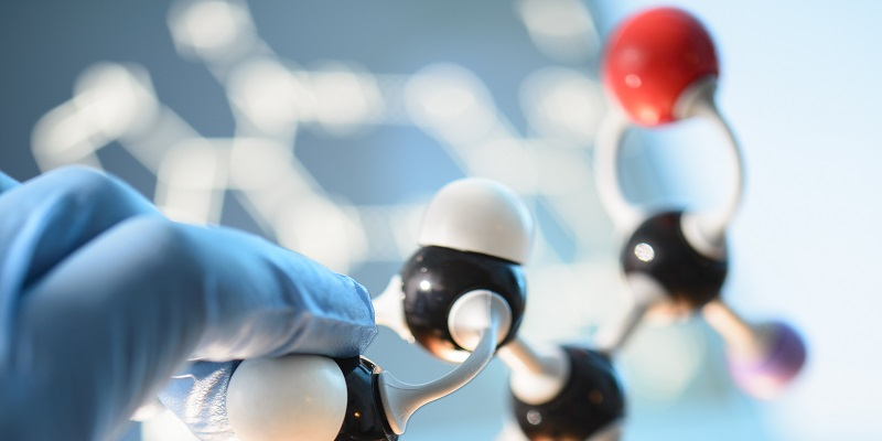 A scientist holding a molecule model
