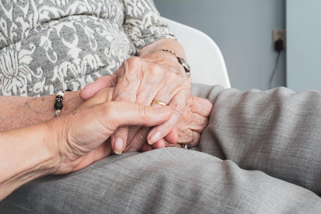 Particolare di un giovane uomo che stringe le mani di una donna anziana con alzheimer con intenzione di comunicare sicurezza.