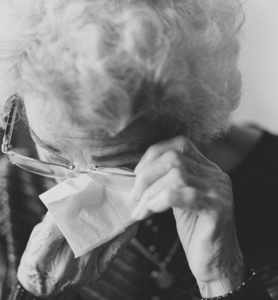 Donna anziana che si asciuga le lacrime agli occhi con un fazzoletto, frustrata dal non riuscire a comunicare efficacemente i suoi bisogni, i suoi sentimenti.