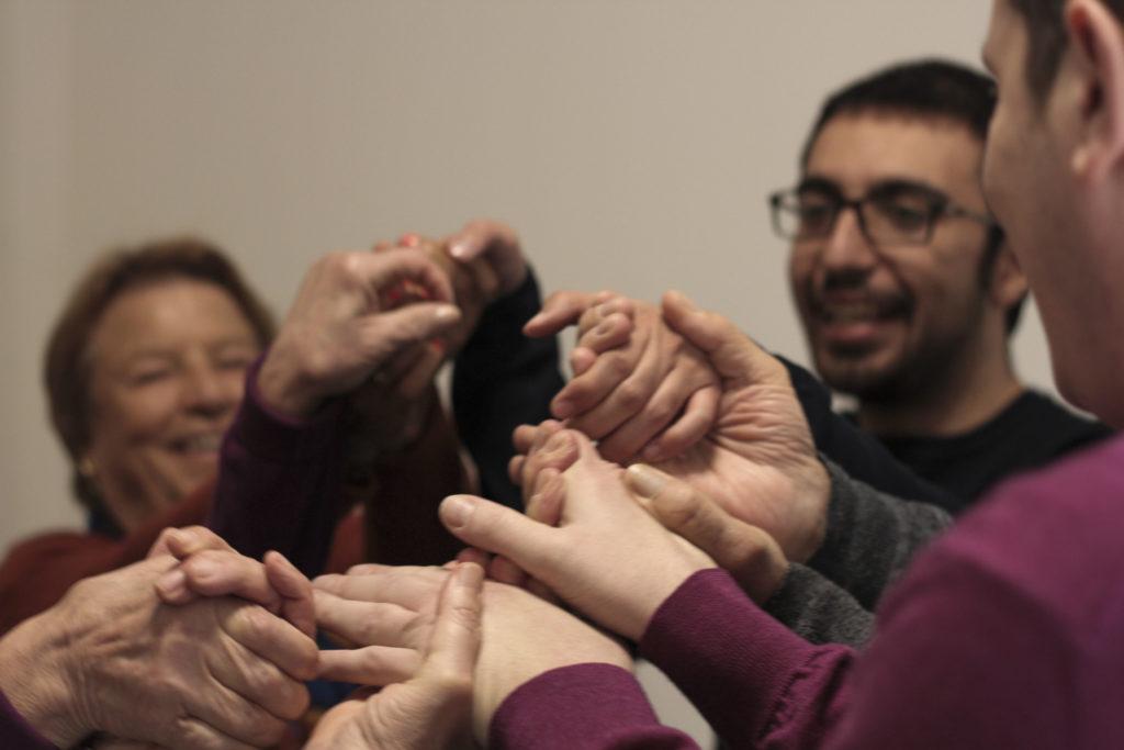 persone durante fisioterapia stringono le mani